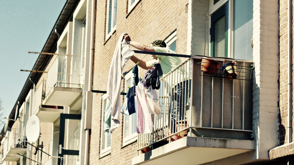 Person hanging laundry on balcony